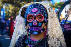 Girl wearing colorful sugar skull mask and lace veil for Dia de. Los Muertos/Day of the Dead stock image