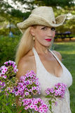 Girl wearing Cowgirl hat by Flowers Royalty Free Stock Image