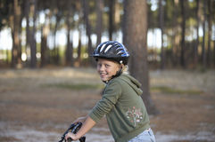Girl (8-10) wearing cycling helmet, sitting on bicycle in woodland, smiling, side view, portrait Stock Image