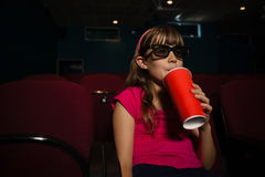 Girl wearing 3D glasses while having drink during movie Royalty Free Stock Image