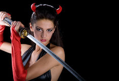 A girl wearing a devil. With a sword Stock Photography