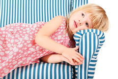 Girl wearing dress is lying on comfortable chair Stock Photography