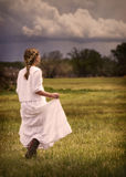 Girl wearing a dress walking in a pasture Royalty Free Stock Photos
