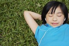 Girl Wearing Earphones While Lying On Grass Stock Photography