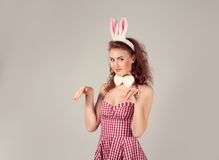 Girl wearing easter bunny costume with eggs in basket Stock Photos