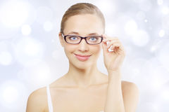 Girl wearing eyeglasses. Light blue background royalty free stock photos