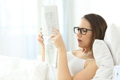 Girl wearing eyeglasses having problems to read a newspaper royalty free stock images