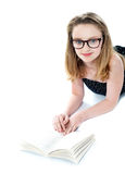 Girl wearing eyeglasses and reading book. Lying on white floor Stock Photography