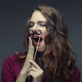 Girl wearing fake mustaches. Royalty Free Stock Image