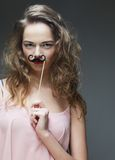 Girl wearing fake mustaches. Royalty Free Stock Photo