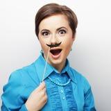 Girl wearing fake mustaches. Royalty Free Stock Photos