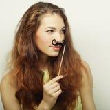 Girl wearing fake mustaches. Royalty Free Stock Photo