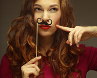 Girl wearing fake mustaches. Stock Images