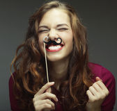 Girl wearing fake mustaches. Royalty Free Stock Photos