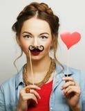 Girl wearing fake mustaches. Stock Photo