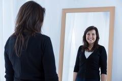 Girl wearing a fake smile. Reflection of girl wearing a fake smile Royalty Free Stock Images