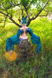 A girl wearing a fever bird's back. On a background of green trees Stock Images