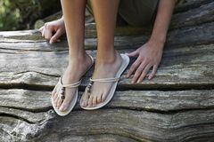 Girl Wearing Flip-Flops Sitting On Tree Trunk Stock Photos