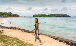 Girl wearing floral maxi skirt walking barefoot on the sea shore, Thailand, Phuket. Bohemian clothing style. Girl wearing floral maxi skirt walking barefoot on stock image