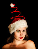 Girl wearing funny red spiral Santa hat Stock Images