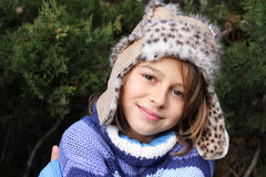 Girl wearing fur hat. Girl with a fake fur leather hat standing in front of a christmas tree, smiling at the camera. Positive feeling Royalty Free Stock Photo