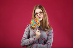 Girl wearing glasses holding big lollipop Royalty Free Stock Photo
