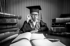 Girl wearing graduation cap posing at table full of books Stock Photography