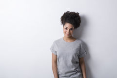 Girl wearing gray t-shirt. Standing near a white wall Stock Image