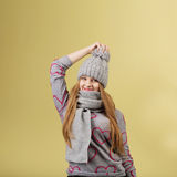 Girl wearing gray woolen cap and scarf against yellow background Royalty Free Stock Photography