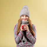 Girl wearing gray woolen cap and scarf holding a red cup against Royalty Free Stock Photo