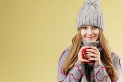 Girl wearing gray woolen cap and scarf holding a red cup against Royalty Free Stock Photos