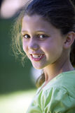 Girl (8-10), wearing green top, standing in summer garden, smiling, close-up, side view, portrait Royalty Free Stock Photo