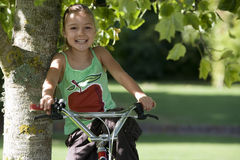 Girl (7-9) wearing green vest top with picture of apple, sitting on bicycle in garden, leaning against tree trunk, smiling, front  Stock Photo