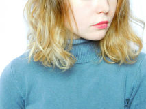A girl wearing grey sweater. A young beautiful girl wearing grey sweater on a white background. Close-up Royalty Free Stock Photography