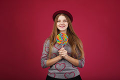 Girl wearing hat holding big striped lollipop Stock Photos