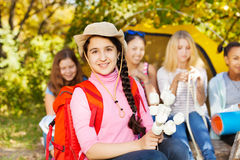 Girl wearing hat holds marshmallow sitting Royalty Free Stock Photography