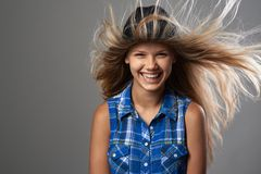 Girl wearing a hat laughing and her hair flutter Royalty Free Stock Image