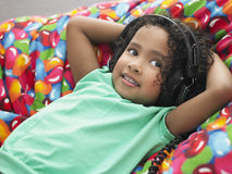 Girl Wearing Headphones Reclining On Beanbag Royalty Free Stock Image