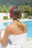 Girl wearing a headset by the swimming pool Royalty Free Stock Images