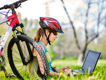 Girl wearing helmet in cycling near bicycle with pc tablet. Stock Images