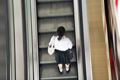 Girl wearing her school uniform on an escalator Royalty Free Stock Photography