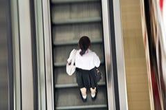 Girl wearing her school uniform on an escalator. BANGKOK, THAILAND -MAY 11: student wearing a school uniform on an escalator on May 11, 2009 in Bangkok, Thailand Royalty Free Stock Photography