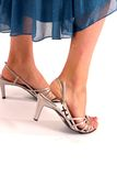 Girl wearing high heel shoes. Woman's feet in white high heel shoes on a white background with blue dress Stock Image