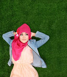Girl wearing hijab lying on grass looking up to copyspace Stock Photography