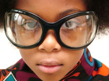 Girl wearing huge bugeye glasses. Young girl wearing huge bugeye glasses against white background Royalty Free Stock Images