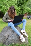 Girl using laptop outside royalty free stock photography
