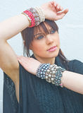 Girl wearing jewelry on both wrists. . An image of a girl wearing lots of silver, cream and red  bangles Royalty Free Stock Image