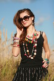 Girl wearing jewelry and sunglasses making hair Stock Images
