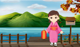 A girl wearing a kimono holding a lantern beside a wooden mailbo Royalty Free Stock Photo