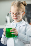 Girl wearing lab coat and protective glasses holding flask with green reagent Stock Photo